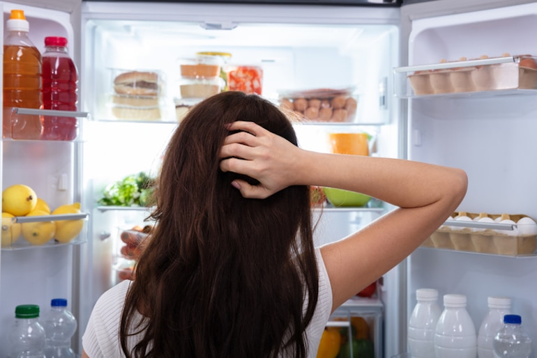 Shot from behind of brunette woman looking into fridge, wondering what to eat during her intermittent fasting open eating window