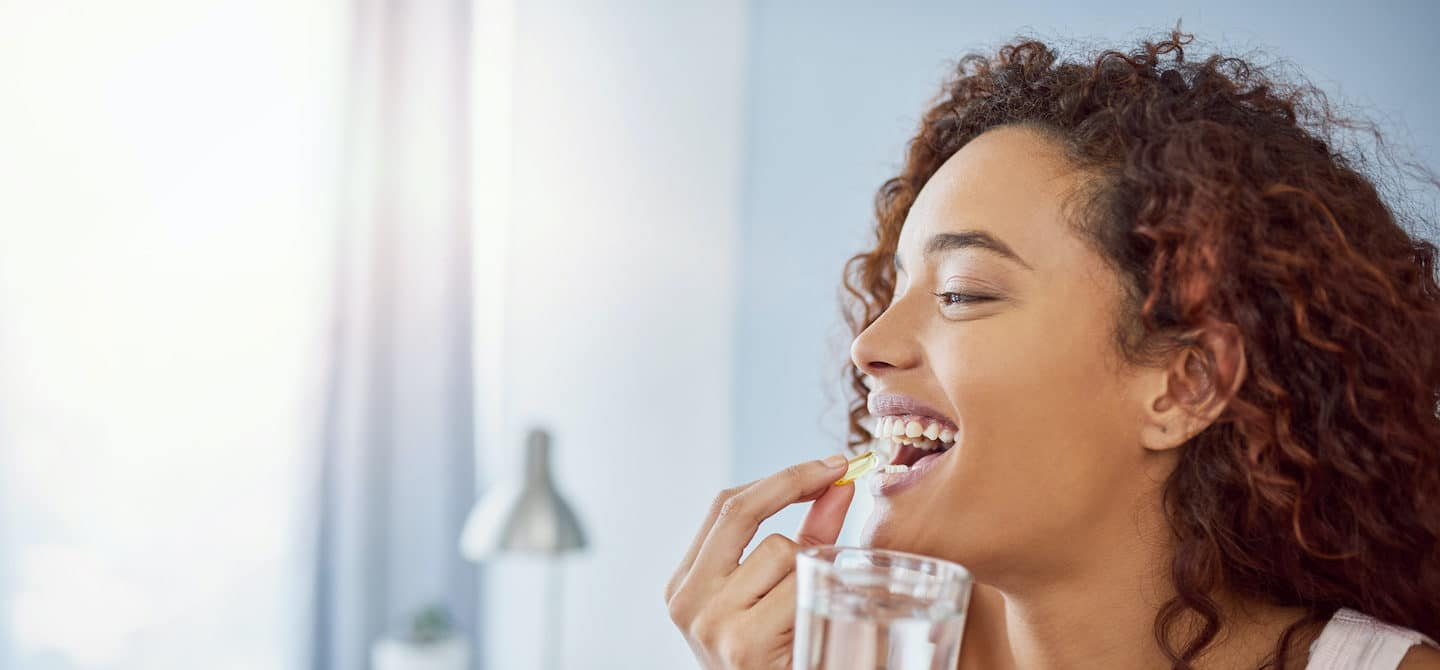 Woman taking a supplement with water to ensure she meets her nutritional needs
