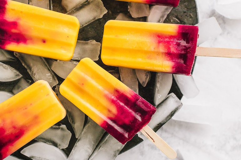 Fruit popsicles for beauty with mango and raspberry on ice