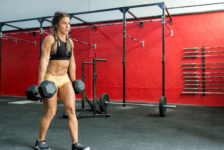 Fit woman in braided pigtails doing the farmers walk exercise of functional training in a gym with heavy dumbbels