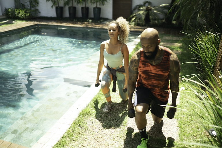 Man and woman doing functional fitness lunges with weights next to their pool