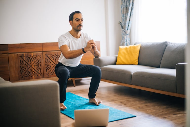 Man doing squats on a blue yoga mat in his living room