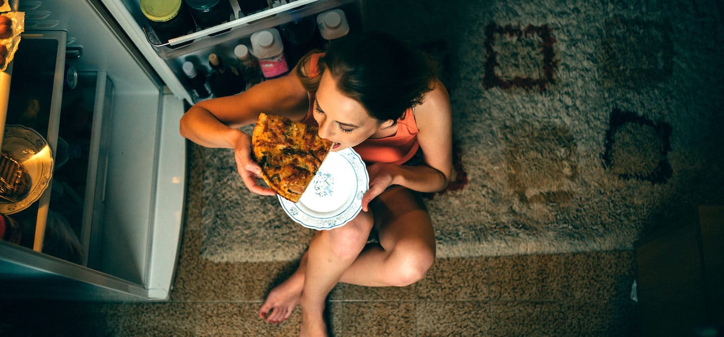 Woman eating pizza on floor in front to fridge to indulge her food craving caused by blood sugar imbalance