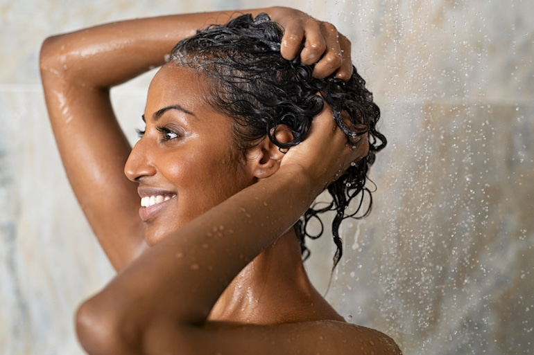 Woman washing her hair infrequently to avoid having greasy hair