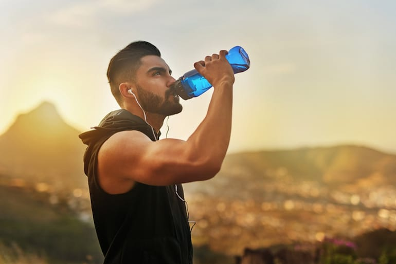 Man drinking water on a hike even though he is intermittent fasting