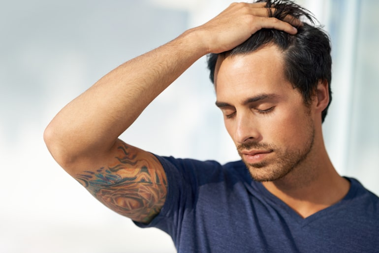 Man running fingers through his thick hair as a benefit of massaging your scalp