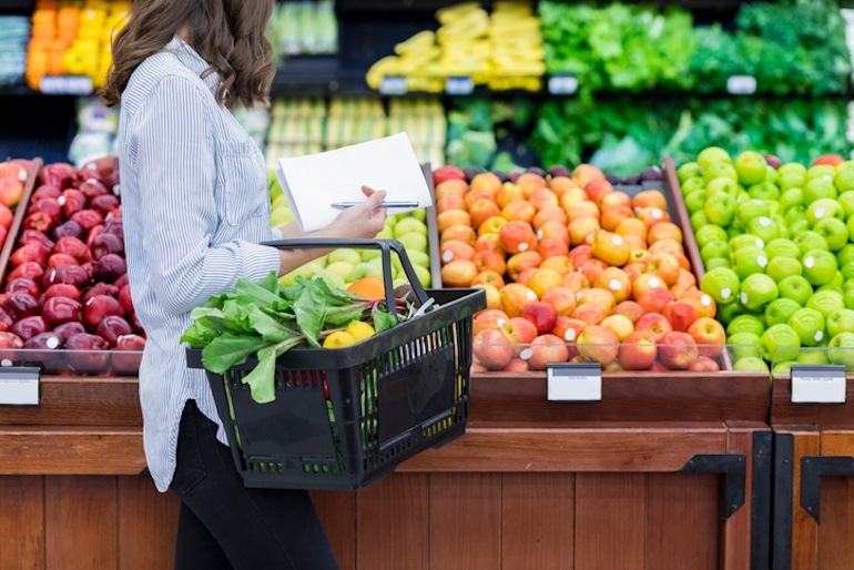 Woman shopping for fresh whole foods as the first step of mindful eating