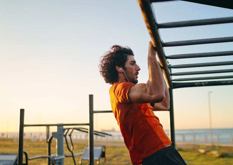 Man doing functional training pull ups at an outdoor gym