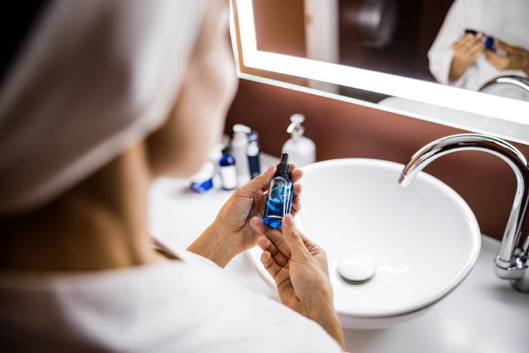 Woman holding a serum at her bathroom vanity