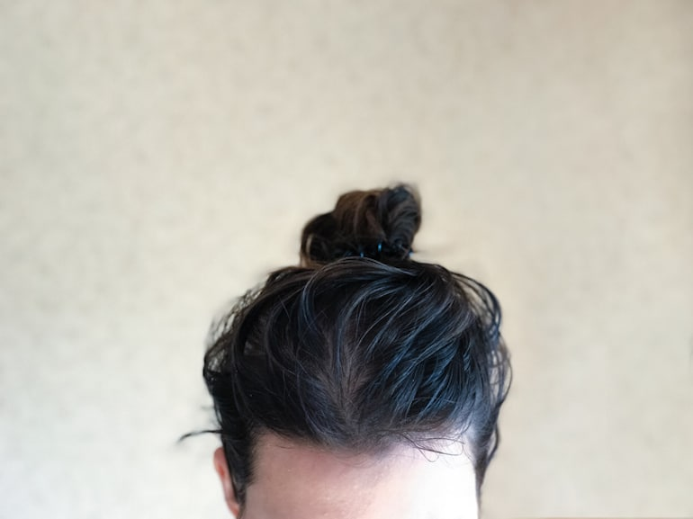 Girl with greasy hair up in a bun