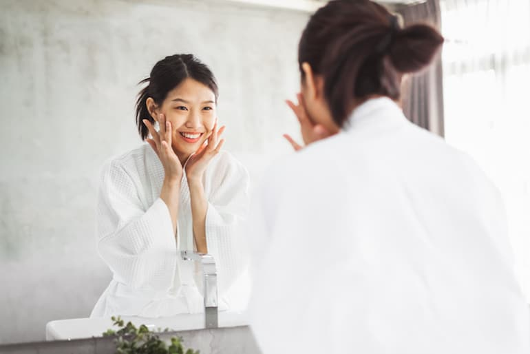 Woman looking in the mirror at her beautiful, clear skin thanks to using the best serum for her skin type and concerns