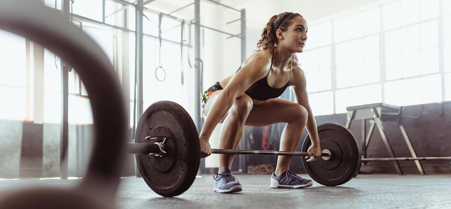Woman doing deadlifts at the gym to complete her functional fitness routine