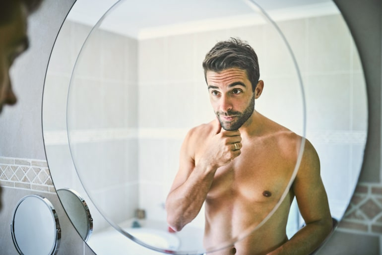 Man looking in bathroom mirror at his great skin thanks to the powerful benefits of face serum