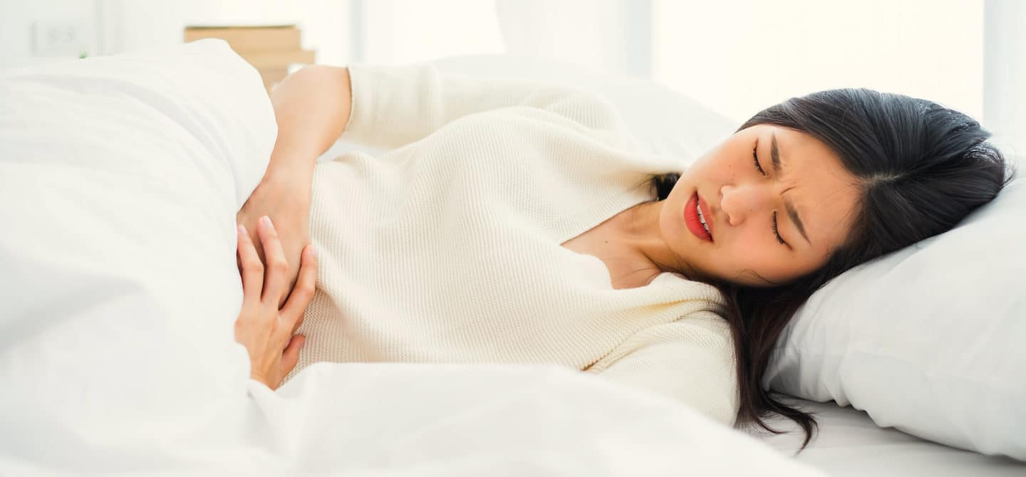 Woman laying in bed suffering from cramps as a common PMS symptom