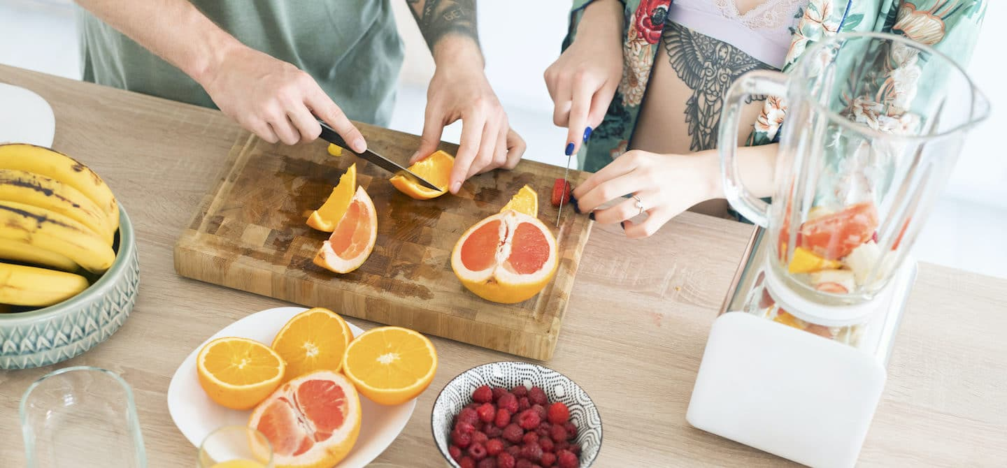 Couple making a morning smoothie at the kitchen island with foods that pack the best vitamins for glowing skin, such as vitamin C