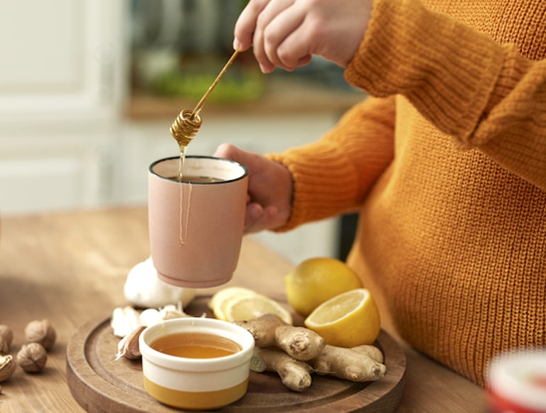 Woman making ginger tea with honey and lemon to relieve cramps