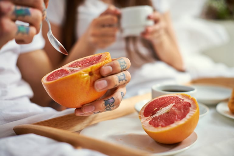 Couple eating grapefruit and coffee in bed
