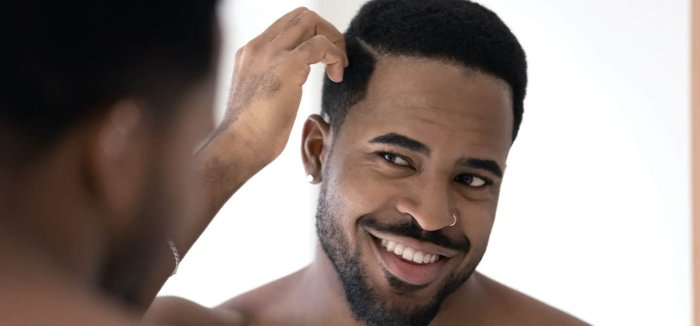 Black man running fingers through his hair, wondering if he should use coconut oil