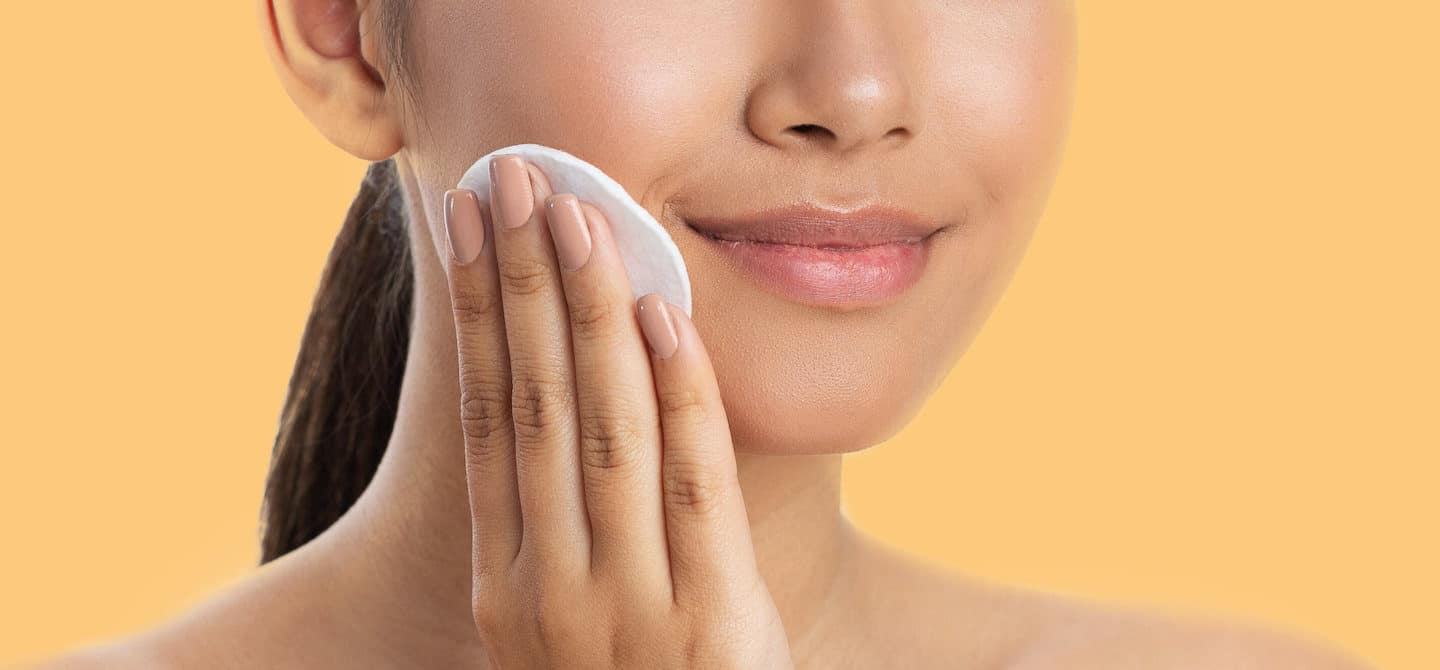Woman exfoliating her sensitive skin with lactic acid toner on a cotton pad