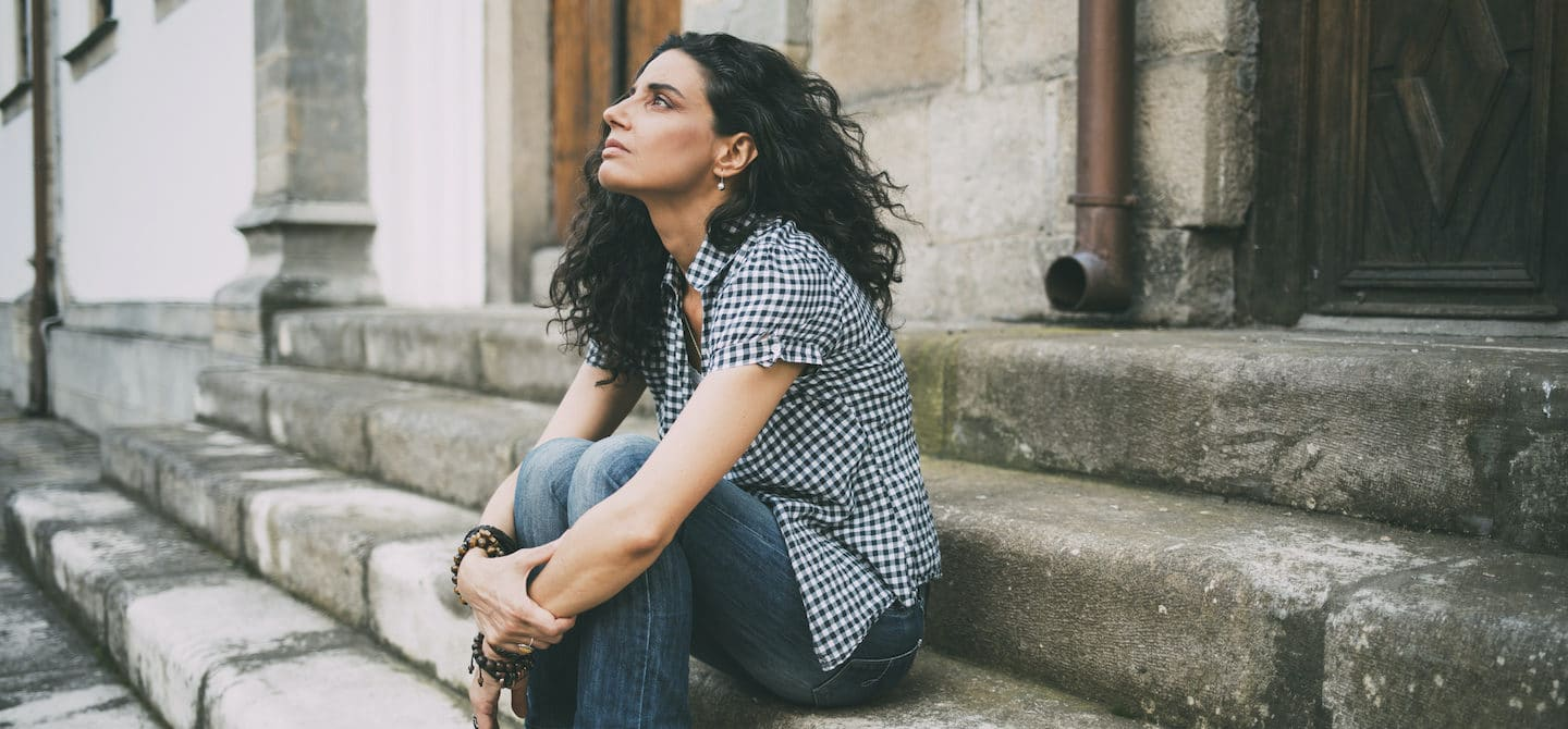 Woman sitting on steps curled up from stress due to hormone imbalances, looking at the sky