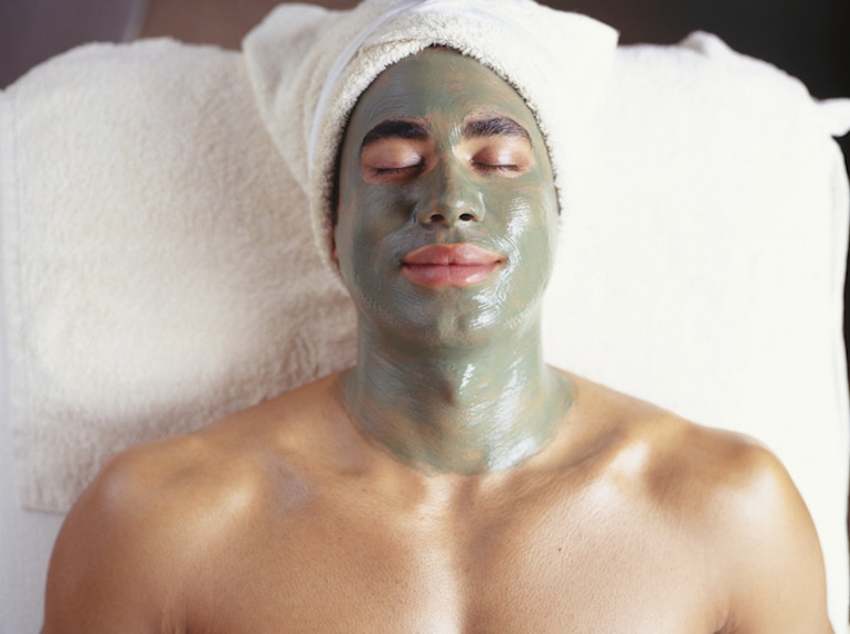 Man at spa with skin-clearing green face mask for acne