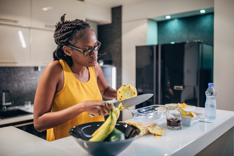 Woman cutting pineapples since they can help reduce cramps