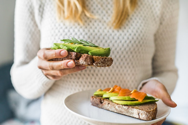 Blonde woman holding toast with salmon and avocado, two of the best foods for cramp relief and reducing PMS pain