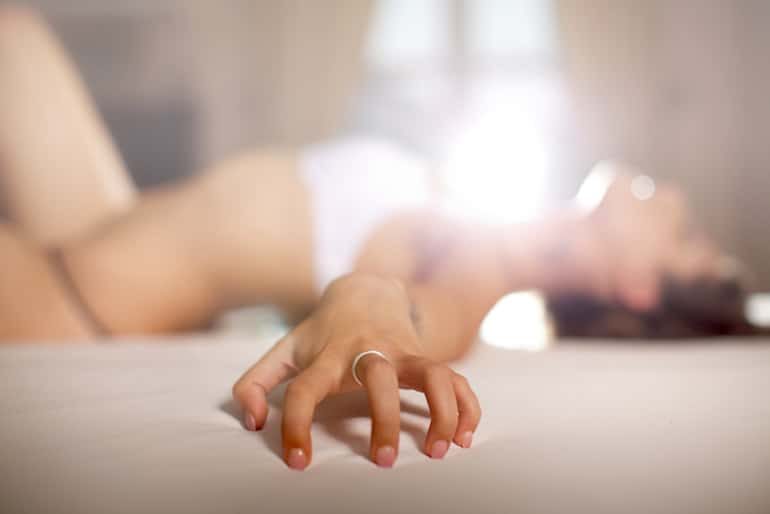 Woman clutching bed having an orgasm and experiencing the benefits of sex and healthy skin