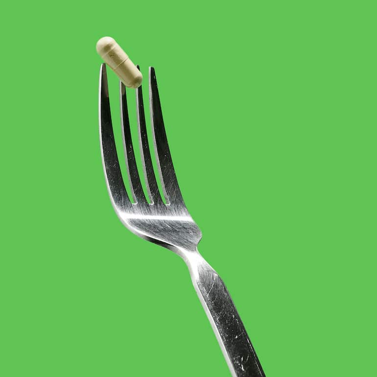 Probiotic capsule on a fork to illustrate the question, should you take probiotics with food?