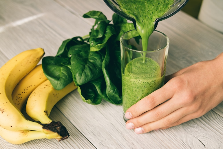 Woman pouring a smoothie with spinach from blender to boost her hyaluronic acid levels