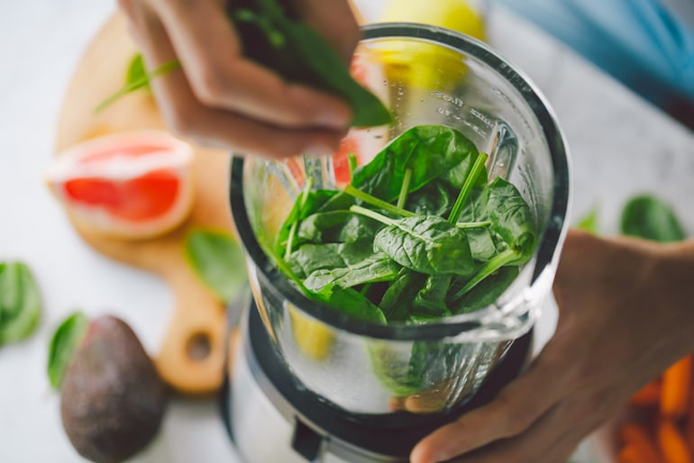Person making a smoothie with spinach, avocado, and grapefruit, some of the top foods with the best vitamins for glowing skin