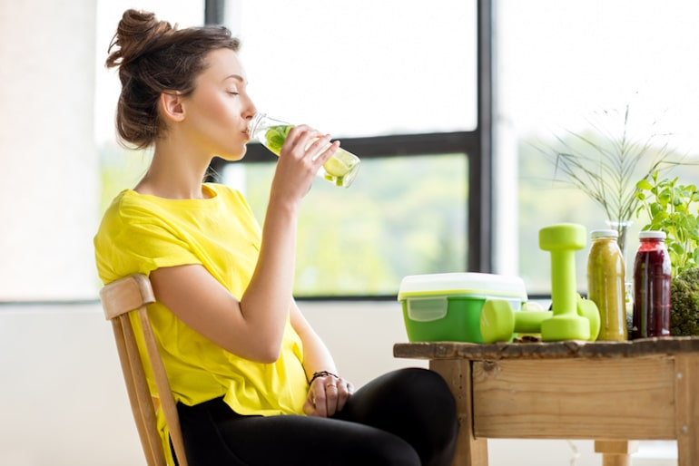Woman drinking water infused with fruit and taking the best vitamins for glowing skin