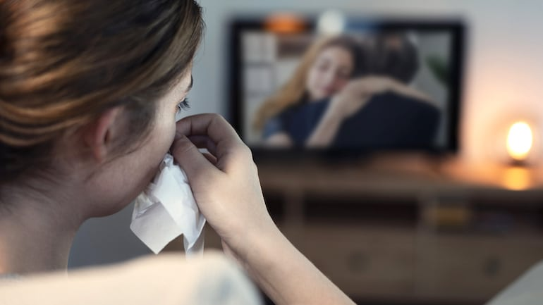 Woman experiencing the health benefits of crying while watching a sad film