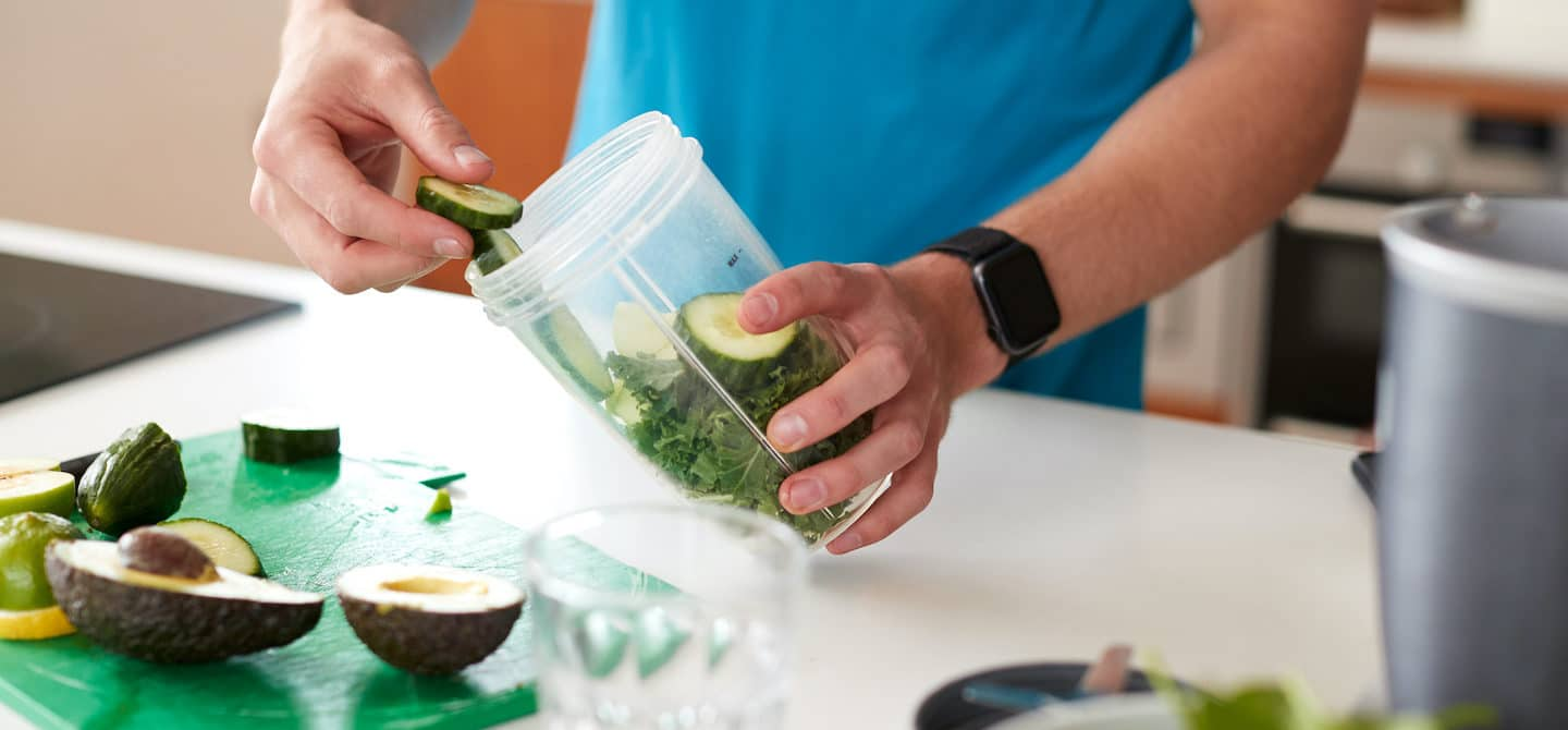Active man making a green smoothie as an easy way to detox the body daily and naturally