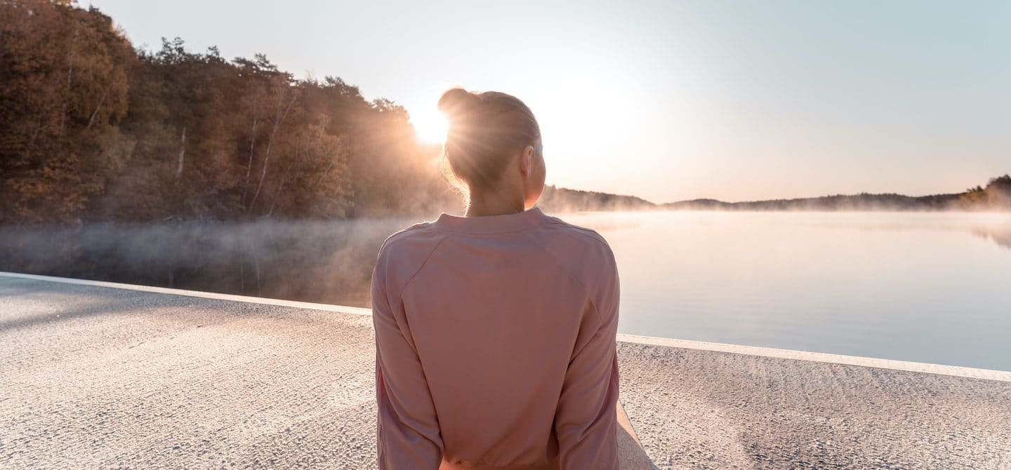 Woman sitting by a lake at sunrise, enjoying the minimal lifestyle, simple joy of living, and psychological benefits of minimalism