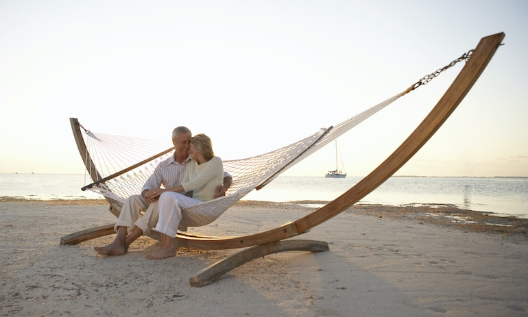Mature couple in love and happy on hammock on the beach, illustrating that your sex life is one of the top things that get better with age