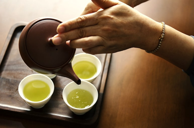 Woman pouring green tea in glasses, one of the best foods for brain health thanks to antioxidants and caffeine