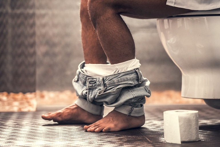 Man on toilet to illustrate butt care, healthy bowel movements, and anal health