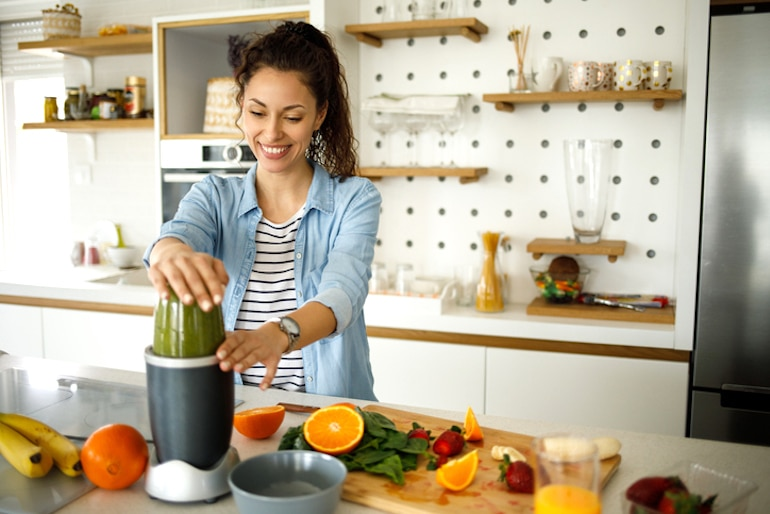 Woman blending a high-fiber green smoothie to have better types of poop