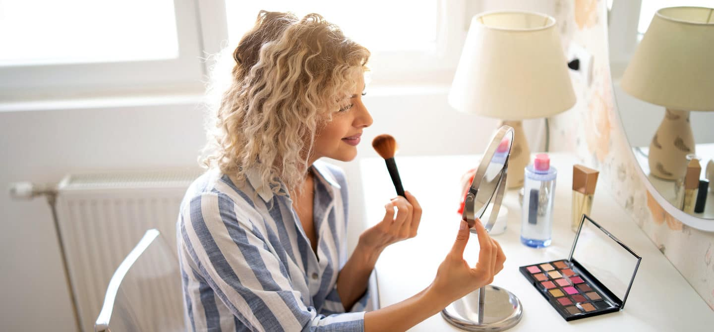 Woman applying makeup at her vanity, looking at the mirror, wondering if her makeup ages skin