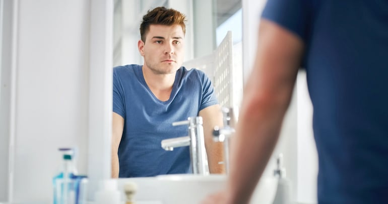 Man evaluating toxic positivity in mirror