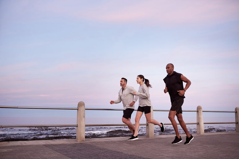 Friends running on the boardwalk as a social, easy way to detox your body naturally