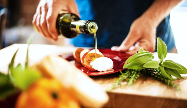 Man pouring extra virgin olive oil for caprese