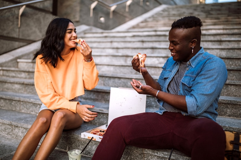 Young couple eating pizza outdoors, a food that can produce free radical damage