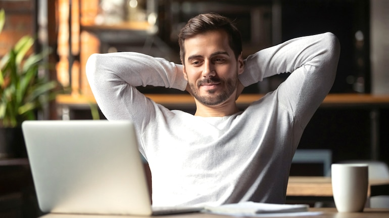 Serene man in front of laptop, happy and relaxed from adopting the inbox zero method