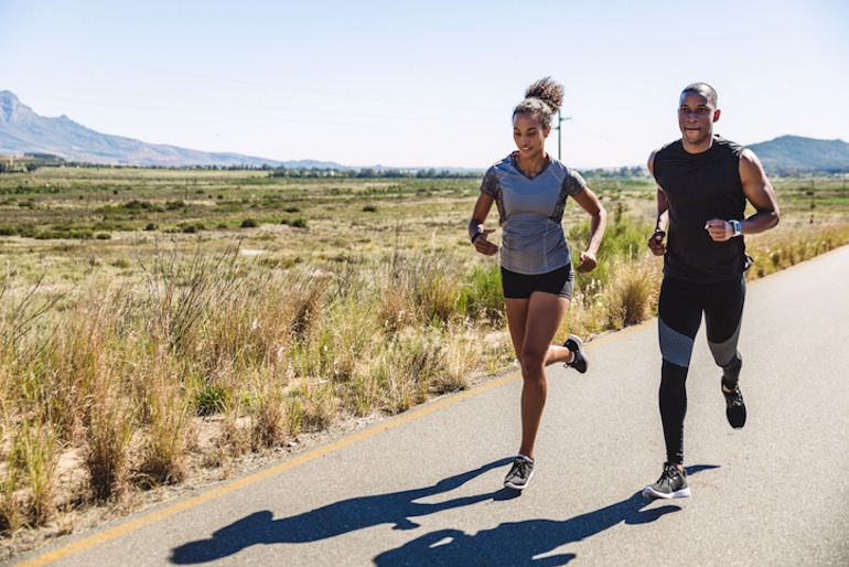 Man and woman running in nature, to exercise both their brains and bodies for many health benefits