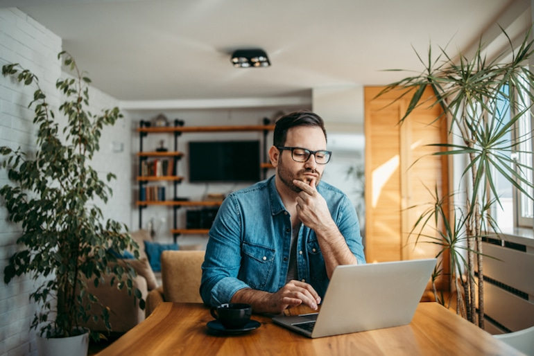 Puzzled man searching for answers on computer, illustrating poor long-term memory formation from excessive internet use