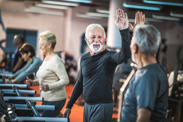Happy senior men high-fiving at the gym, illustrating positivity and happiness as the best things that get better with age