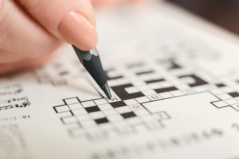 Woman doing a crossword puzzle, one of the best ways to exercise your mind