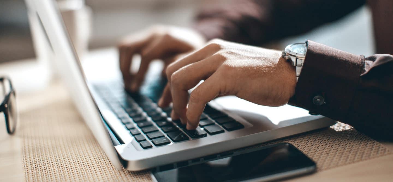 Man's hands at work on laptop, implementing the inbox zero method